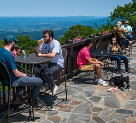 Guests and dog enjoying terrace seating at Big Meadows Lodge in Shenandoah National Park